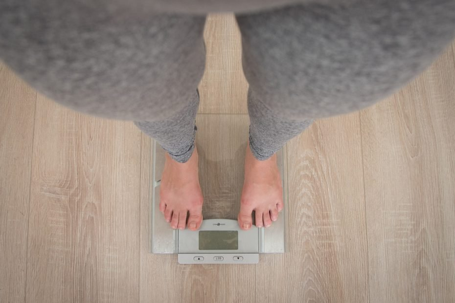 A lady standing on a set of scales.