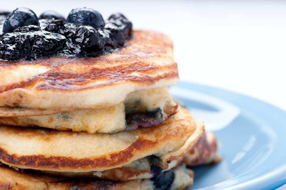 A stack of blueberry pancakes with blueberries piled on top.