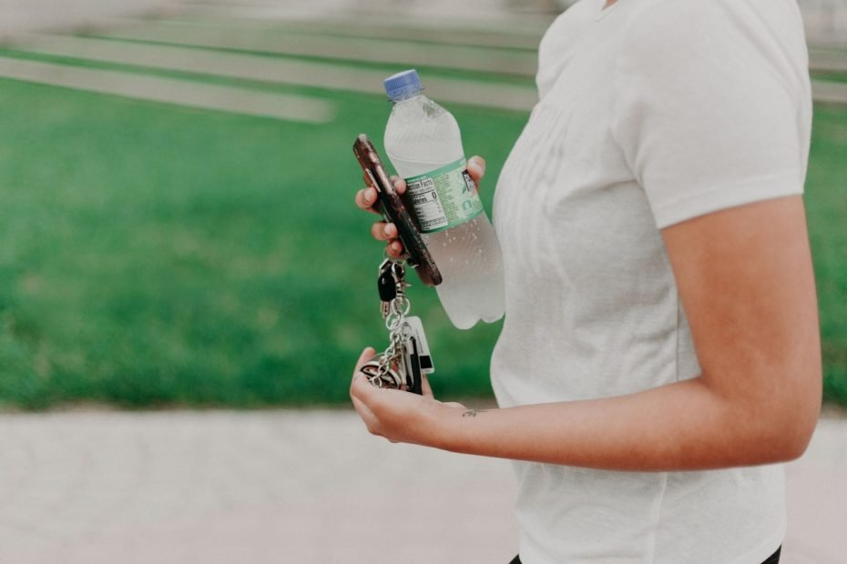 Woman carrying a bottle of water.