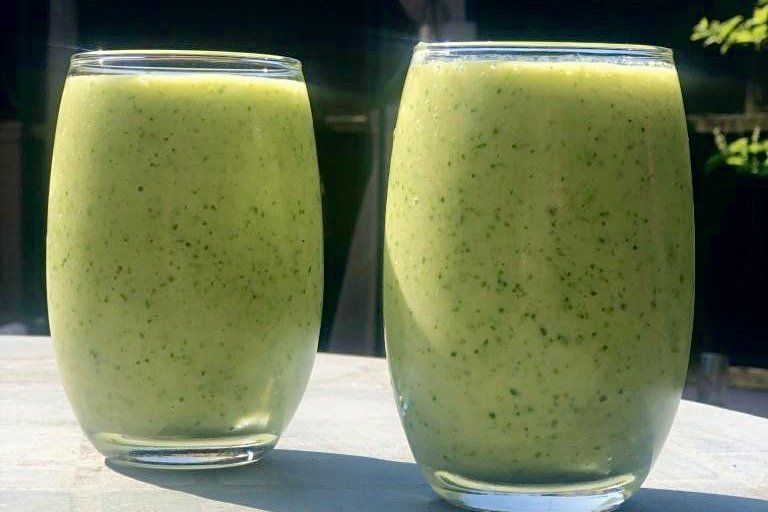 A green smoothie on a garden table on a sunny day.