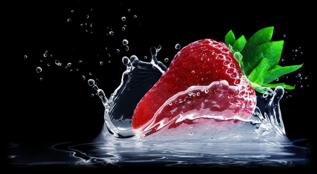 A single strawberry splashing into water.