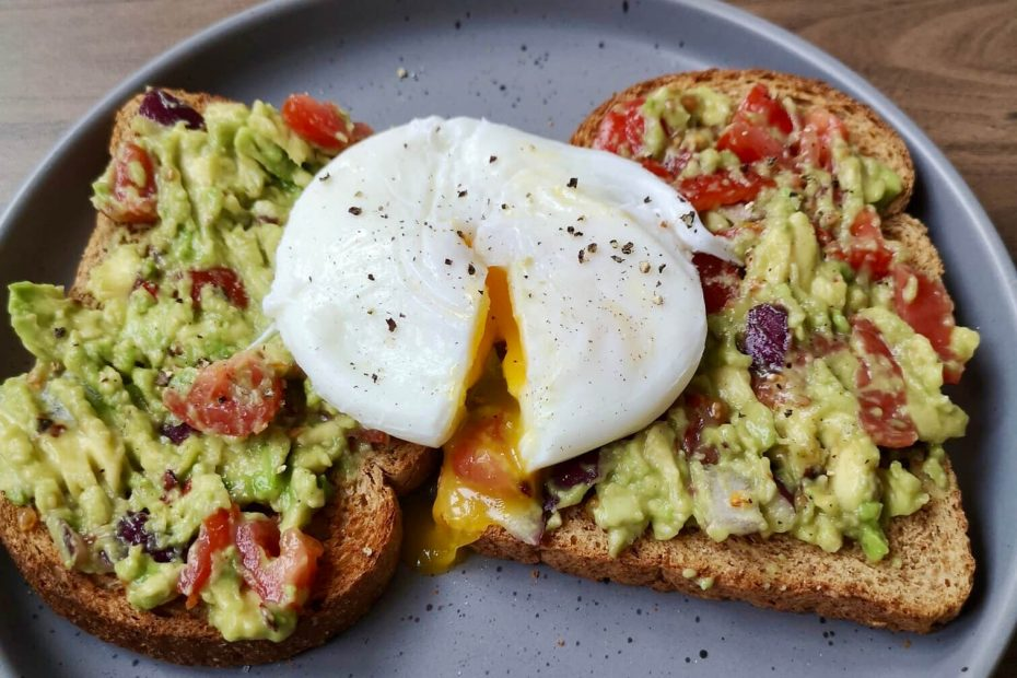 Smashed avocado on toast with a runny egg and chopped cherry tomatoes.
